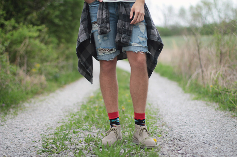 The Kentucky Gent for CAT Footwear's Summer Festival Style campaign in BDG Tank, Devil's Harvest Plaid, Levi's Denim Shorts, Richer Poorer Socks, and Caterpillar Suede Chukka Boots