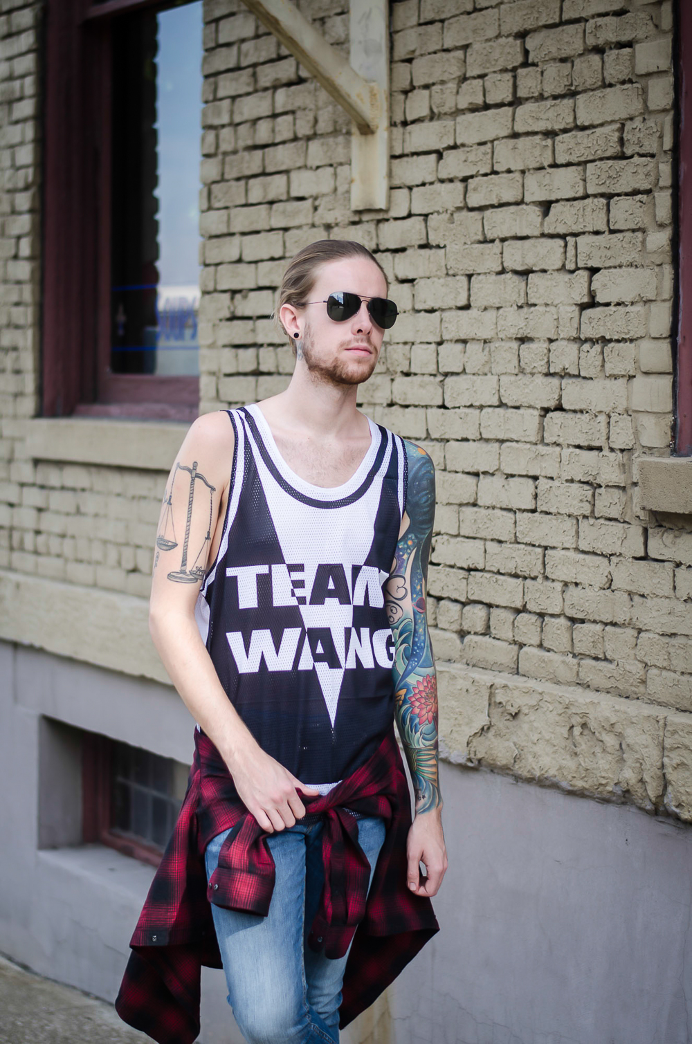 The Kentucky Gent, a Louisville, Kentucky men's fashion blogger, in ALEXANDERWANGXHM Jersey Tank Top, H&M Denim Jeans, H&M Plaid Shirt, Converse Chuck Taylors, and Ray-Ban Aviator Sunglasses.