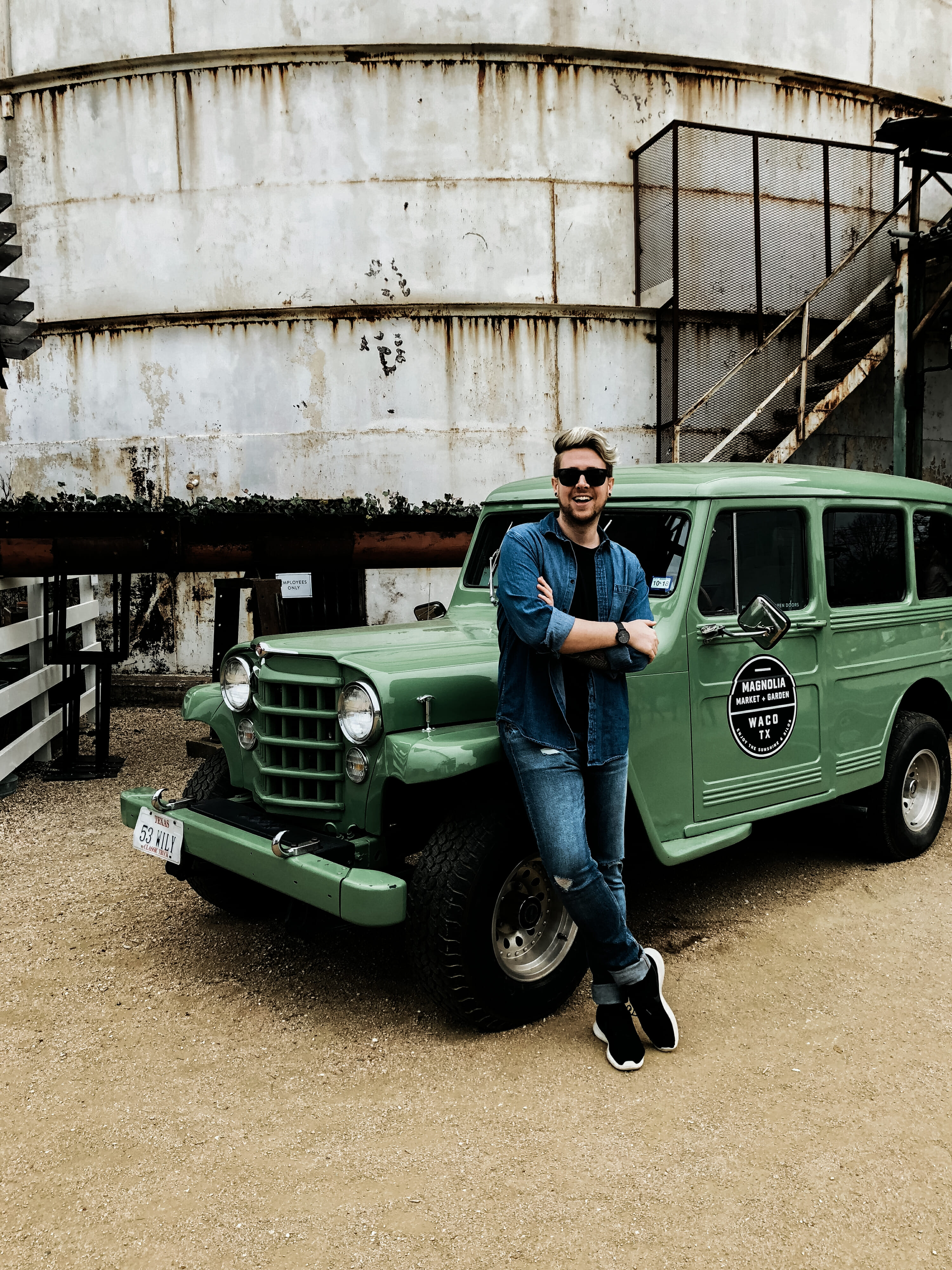 blonde man in front of green truck